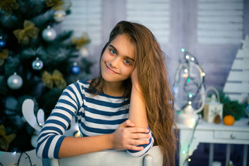 Happy girl in Сhristmas time. girl in background New Year's interior. Beautiful girl in Christmas and New year. young girl with long hair sitting on chair.