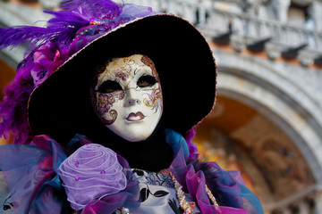 Colorful carnival lilac-violet mask and costume at the traditional festival in Venice, Italy