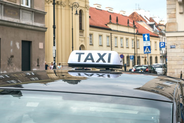 Sign and symbol of a taxi on the roof of a black car in the historic part of the old city