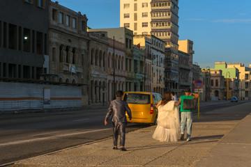 Los novios se van después de la sesión de fotos en el malecón de la Habana.