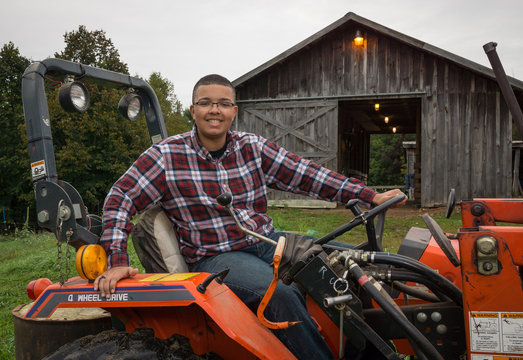 Young man on a tractor in front of a barn