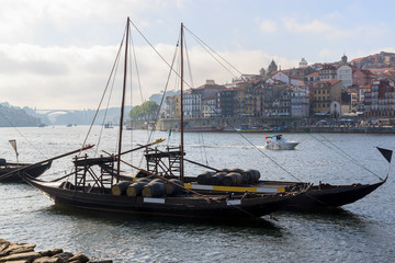 View of the Ribera from the opposite shore of the river Douro, Porto, Portugal. Colorful houses on the embankment.  Barrels of port on boats.