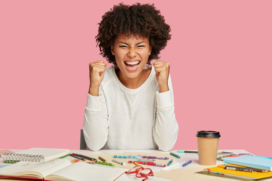 Photo of overjoyed African American architect keeps fists clenched, smiles broadly, squints face, poses at desktop, creats something, rejoices promotion, isolated over pink studio background