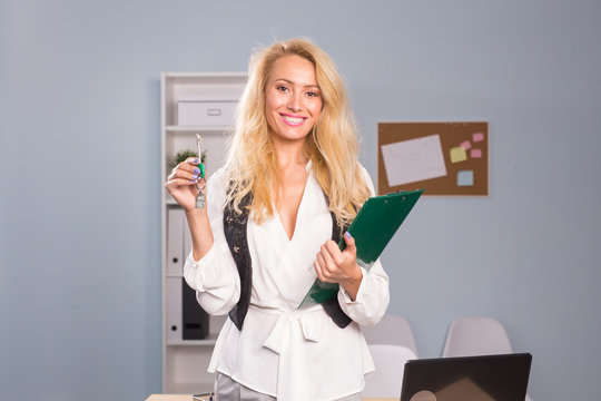 Business and people concept - beautiful blonde realtor with files show keys from a new flat