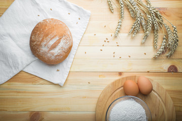 kitchen still life from flour, wheat ears, bread and eggs