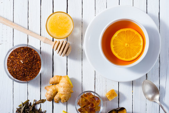 cup of tea, different leaves, honey, lemon ginger and brown sugar on white wooden table background