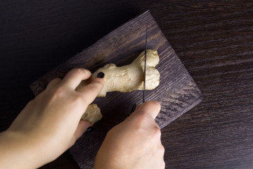 top view woman cut ginger on a wooden board
