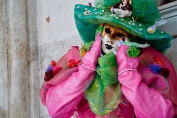 Colorful carnival pink-green mask and costume at the traditional festival in Venice, Italy
