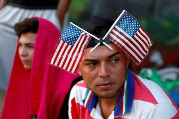 Central American migrant, part of a caravan trying to reach the U.S., is pictured with U.S. flags on his head as he waits to reunite with more migrants, in Tecun Uman