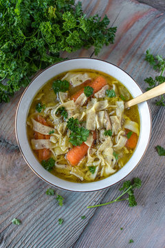 Homemade chicken soup with egg noodles, carrots, and celery flat lay