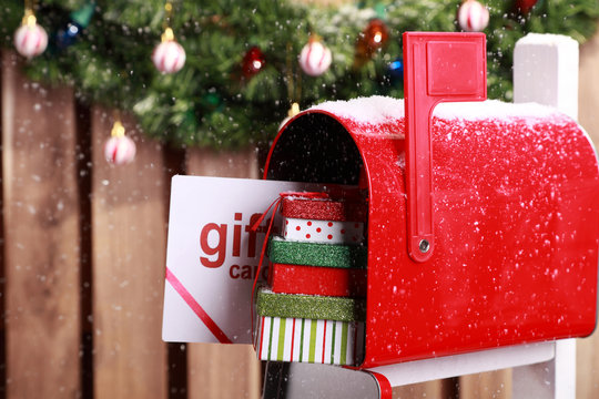 Red mailbox with Christmas gift card and presents