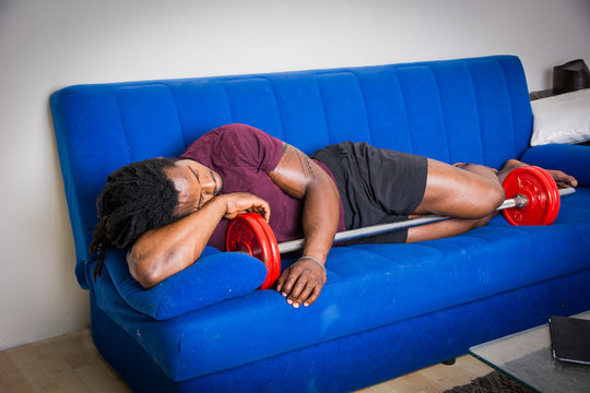 Young strong black male sleeping on couch embracing barbell.