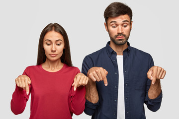 Shot of curious woman and man have surprised expressions, point down with both index fingers, notice something incredible on floor, isolated over white background. Horizontal view. Advertisement