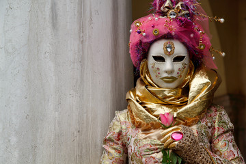 Colorful carnival pink-gold mask and costume at the traditional festival in Venice, Italy