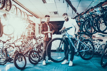 Consultant Shows Bicycle to Client in Sport Shop