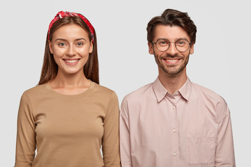 Wall Mural - Funny young colleagues chuckle and smile broadly, have day off after hard working week, stand shoulder to shoulder against white studio wall, express good emotions and feelings. Facial expressions