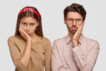 Wall Mural - Photo of displeased woman and man have sullen expressions, stand closely to each other, express negative emotions, isolated over white background. People, relationships and facial expressions concept
