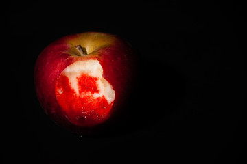 An apple with a bloody bite mark on a black background