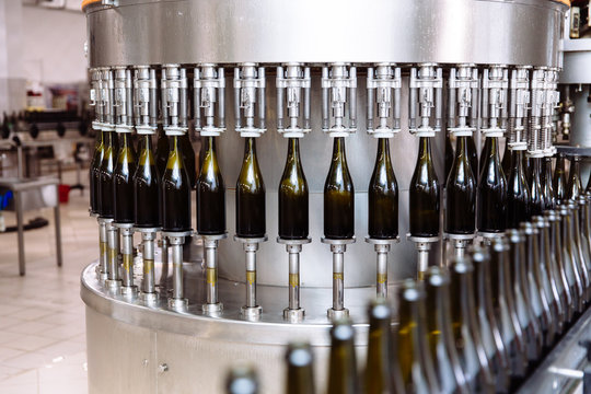 Glass bottles on the automatic conveyor line at the champagne or wine factory. Plant for bottling alcoholic beverages.
