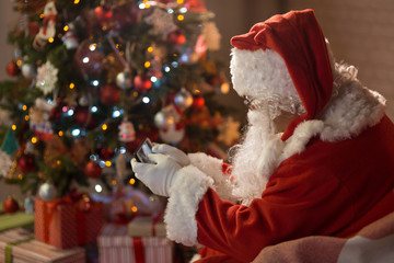 Merry Christmas. Santa Claus at home by the fireplace and Christmas tree