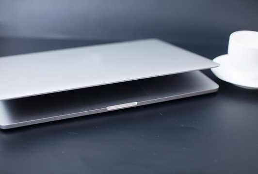 Silver laptop half closed on dark background with cup of coffee near