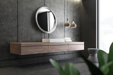 Sink and mirror in concrete bathroom corner