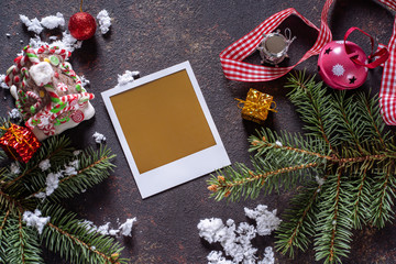 Christmas greeting card or photo frame over wooden table with snow fir tree.