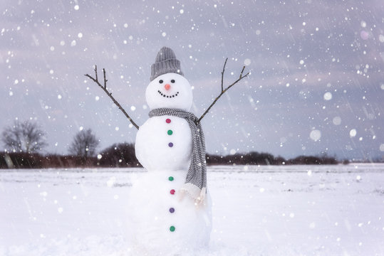 Cute smiling snowman in snowfall, happy winter concept