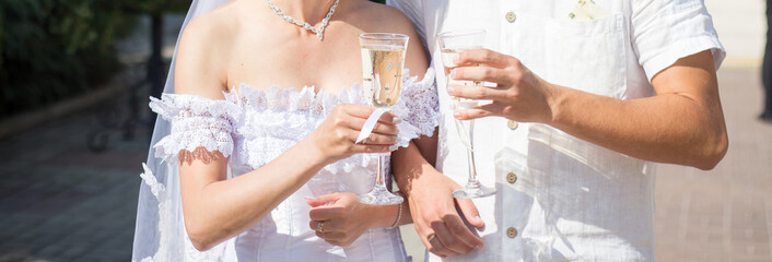 Newlyweds holding champagne in their hands