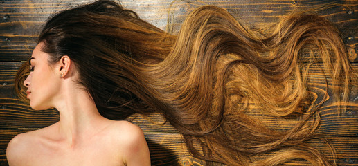 Very long hair on wooden background. Beautiful model with curly hairstyle. Hair Salon concept. Care and hair products.