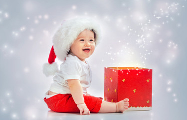 Toddler boy with santa hat opening a gift box in snowy day