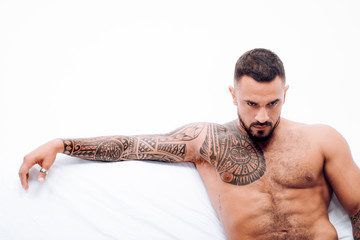 Nude male model lies in white bed. Muscular tattooed Man ready to St Valentine's Day. Muscular man alone in bed - Happy Valentine's Day.