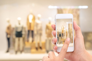 Woman hands Taking a picture with a smart phone in shopping mall with blurred image of clothes shop.