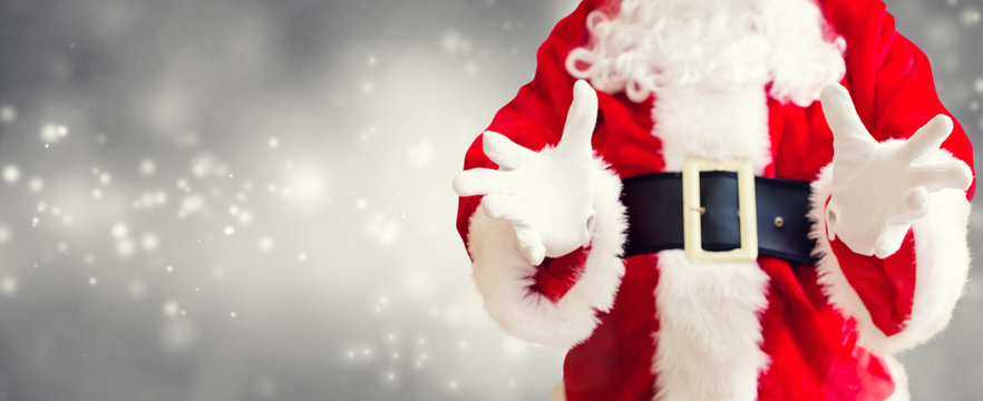 Santa with holding gesture on a shiny light background