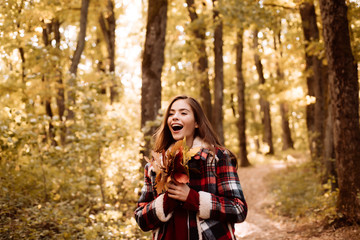 Beautiful young happy girl with a bright red-yellow leaf in the park. Perfect Woman Fashion Model with Fall Maple Leaf Outdoors. Autumn landscape. Autumn woman having fun at the park and smiling.