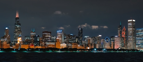 Downtown Chicago cityscape skyline at night with Lake Michigan in the foreground