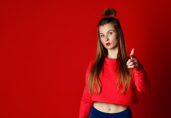 Portrait of a confident fitness woman pointing finger at camera
