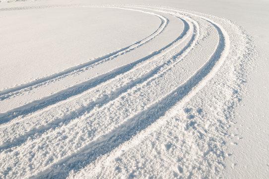 Car tire tracks in fresh snow.