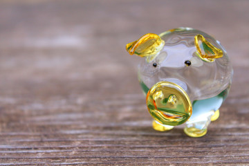 Yellow glass transparent pig on an old wooden board. Close-up. Background. Texture.
