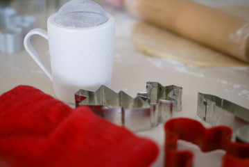 Red towel, white sifter, red and silver cookie cutters, rolling pin with dough on light counter top