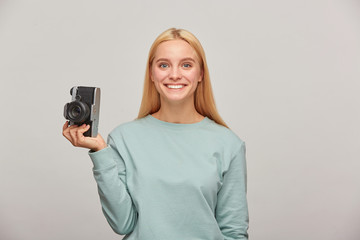 Lovely girl photographer looks happily smiling, holding a retro vintage photo camera in one hand, gets pleasure from the shooting process, wearing blue casual sweatshirt, over grey background