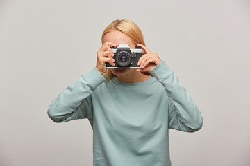 Girl covering her face with the camera making a photo session. Photographer taking photo, working in studio, in-door photography, dressed blue sweatshirt, over grey background