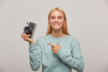 Lovely girl photographer taking a photo session, inspired by the retro vintage photo camera in hand, pointing on it with finger, dressed in blue sweatshirt, on grey background