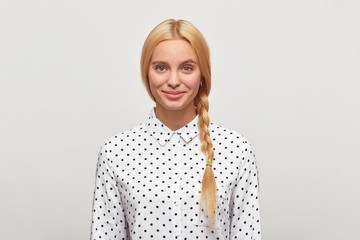 Beautiful diligent blonde woman with blue eyes, braid, feels happy, tenderly smiles, wears white shirt with black polka dots. Modest, excellent student, came to interview. Over white background