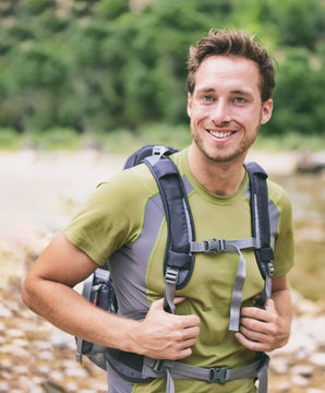 Active young man portrait hiking outdoors. Young male hiker smiling happy wearing backpack for backpacking camping travel trip outdoors during hike in forest nature. Caucasian male model.
