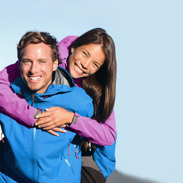Happy hikers couple active lifestyle hugging laughing outdoors on trek hike. Healthy young people on adventure wearing blue purple jackets. Interracial relationship, Asian woman, Caucasian man.