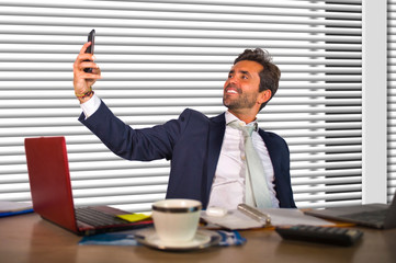 lifestyle portrait of young happy and successful business man working relaxed at modern office by window computer desk talking selfie picture smiling confident