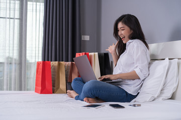 cheerful woman using laptop computer to shopping online on bed
