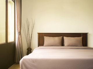 Empty double wooden bed in luxury and natural style bedroom is simple decorated with two pillow. Copy space.