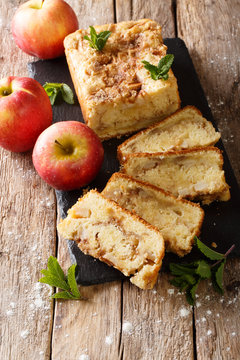 Rustic style apple bread with cinnamon and mint close-up on a wooden background. vertical